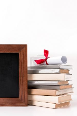 Diploma on stack of books with empty blackboard isolated on white