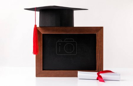 Photo for Square academic cup on empty blackboard and diploma isolated on white - Royalty Free Image