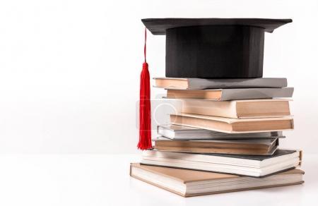 Photo pour Carré chapeau académique sur la pile de livres différents isolé sur blanc - image libre de droit