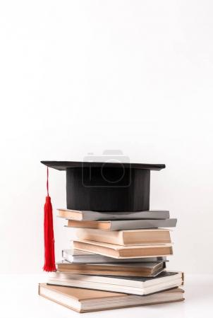 Academic cap on stack of different books isolated on white