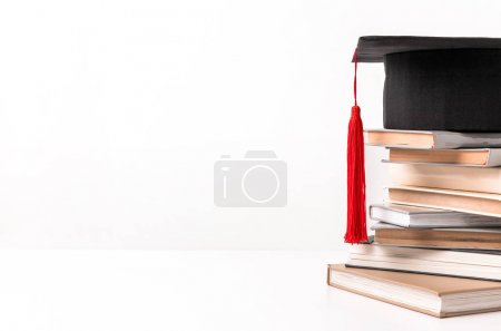 Photo for Cropped view of quare academic cap on stack of different books isolated on white - Royalty Free Image