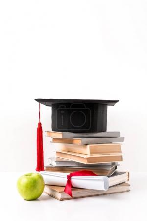 Pile of books with academic hat, diploma and apple isolated on white