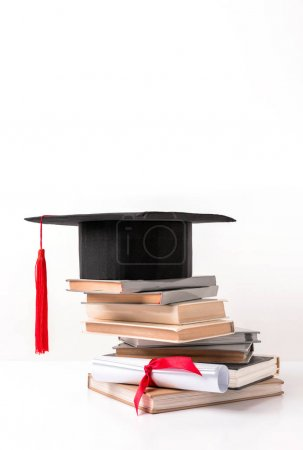 Academic cap on pile of books and diploma isolated on white