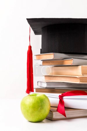 Apple near diploma and pile of books with academic cap on top isolated on white