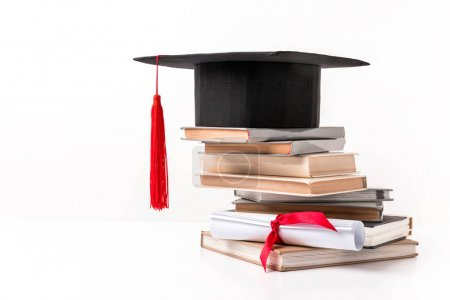 Academic cap on stack of books isolated on white