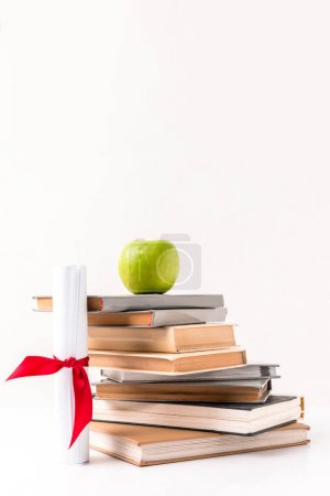 Diploma with stack of books with apple on top isolated on white