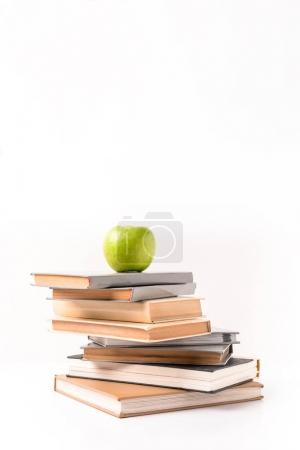 Apple on pile of books isolated on white