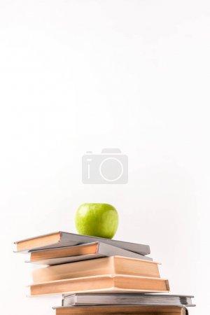 Photo pour Vue d'angle faible de la pile de livres avec apple en haut isolé sur blanc - image libre de droit