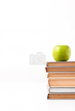 Cropped view of stack of books with apple on top isolated on white