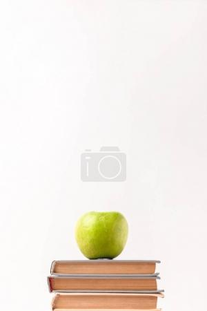 Stack of books with apple on top isolated on white