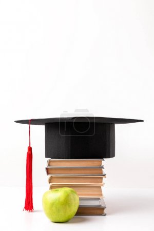 Apple near pile of books with academic cap on top isolated on white