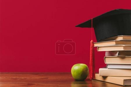 Photo pour Vue recadrée de la pile de livres avec chapeau académique sur le dessus et pomme sur rouge - image libre de droit