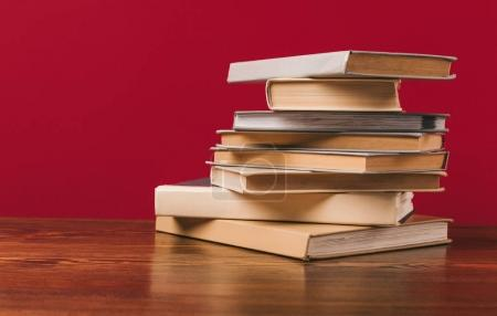 Floor with stack of different books on red