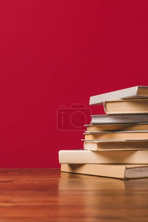 Cropped view of stack of different books on red