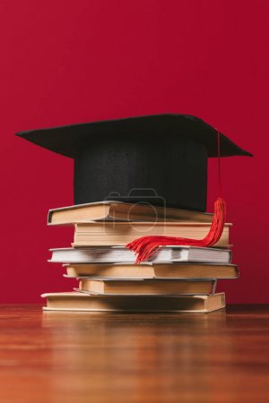Academic cap on top of pile of books on red