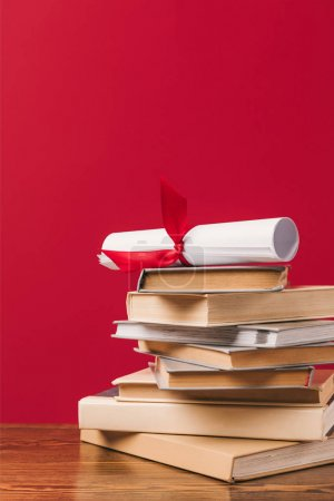 Diploma on top of stack of books on red