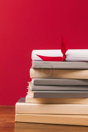 Cropped image of diploma on top of stack of books on red