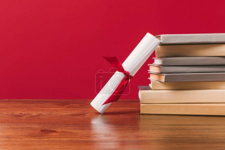 Diploma and stack of different books on red