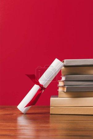 Photo pour Vue recadrée de la pile de livres et diplôme sur rouge - image libre de droit