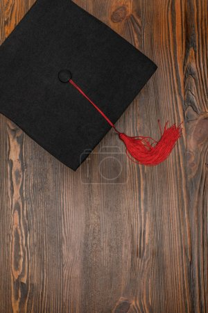 Top view of square academic cap on wood background