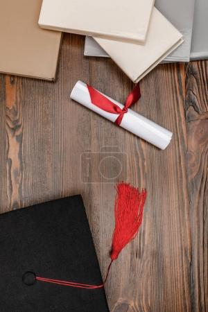 Top view of books, diploma and academic cap on wood background