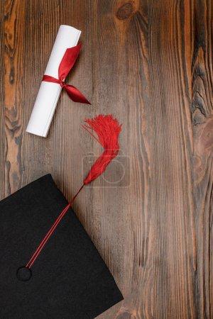 Photo pour Vue du dessus du diplôme et chapeau académique carré sur fond bois - image libre de droit