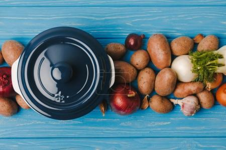 top view of pan with uncooked vegetables on blue table