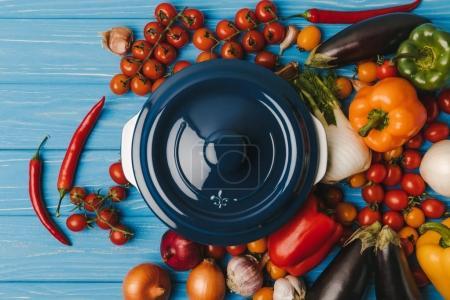 top view of pan between vegetables on blue table