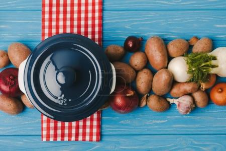 top view of pan and vegetables on blue table
