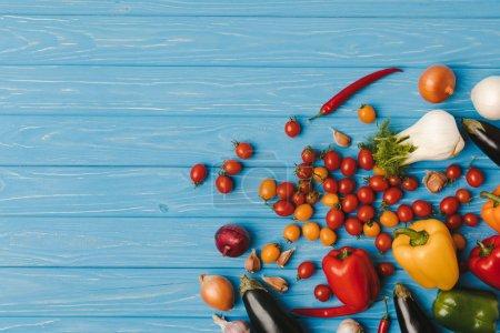 Foto de Vista superior de verduras sin procesar maduros en tabla azul - Imagen libre de derechos