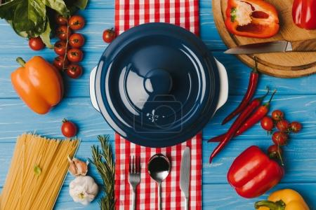 top view of pan and unprocessed vegetables and pasta on blue table