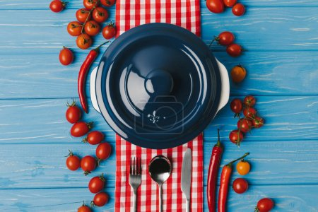 top view of pan, scattered cheery tomatoes and chili peppers on blue table