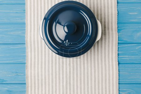 Photo for Top view of pan on napkin on blue wooden table - Royalty Free Image