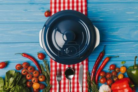 top view of pan and unprocessed vegetables on blue table