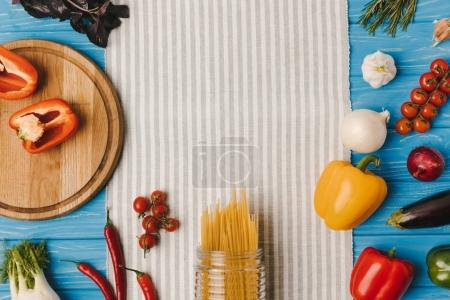 top view of uncooked pasta and ripe vegetables on napkin on blue table