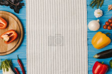 top view of napkin and vegetables on blue table
