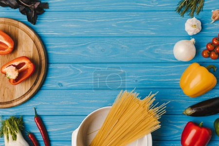 elevated view of uncooked pasta and vegetables on blue table