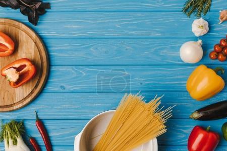 Photo pour Vue des pâtes alimentaires non cuites et des légumes sur table bleue - image libre de droit