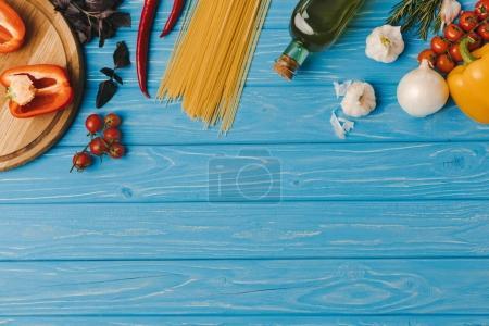 Photo pour Vue du dessus des ingrédients pour la cuisson des pâtes sur la surface bleue - image libre de droit