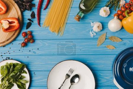 Foto de Vista superior de la placa con un tenedor, cuchara y verduras en la superficie de madera - Imagen libre de derechos