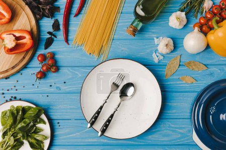 top view of plate with fork and spoon and vegetables on blue table