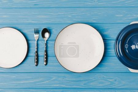 Photo for Top view of fork, spoon and plates on blue table - Royalty Free Image