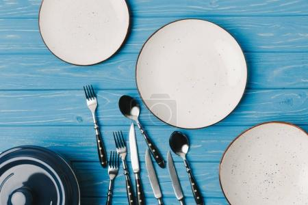 Photo for Top view of plates with scattered forks, spoons and knifes on blue table - Royalty Free Image