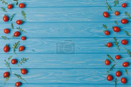 top view of cherry tomatoes with arugula on blue table
