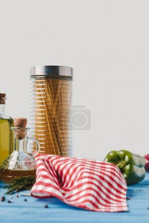 ingredients for cooking pasta on blue table in kitchen