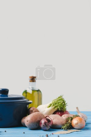 pan with ripe organic vegetables and olive oil on table in kitchen