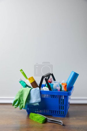 domestic supplies for spring cleaning in blue basket on floor