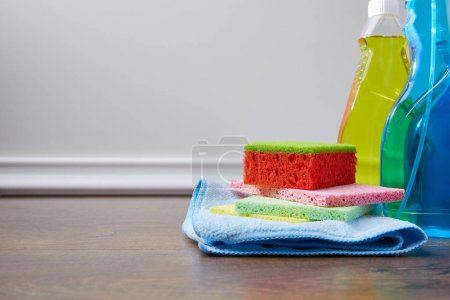 Photo for Bottles with antiseptic liquids and rags for spring cleaning on floor - Royalty Free Image