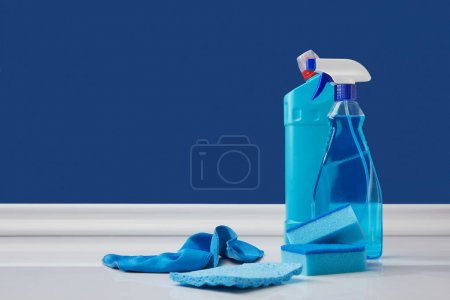 spray, rags and sponges for spring cleaning on blue