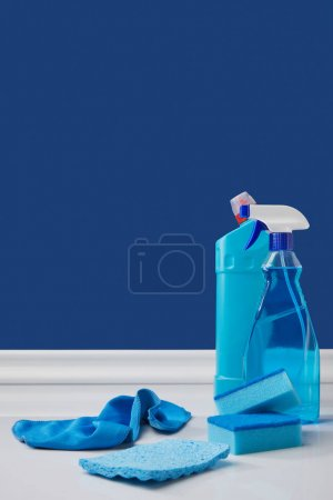 spray, rags and washing sponges for spring cleaning on blue